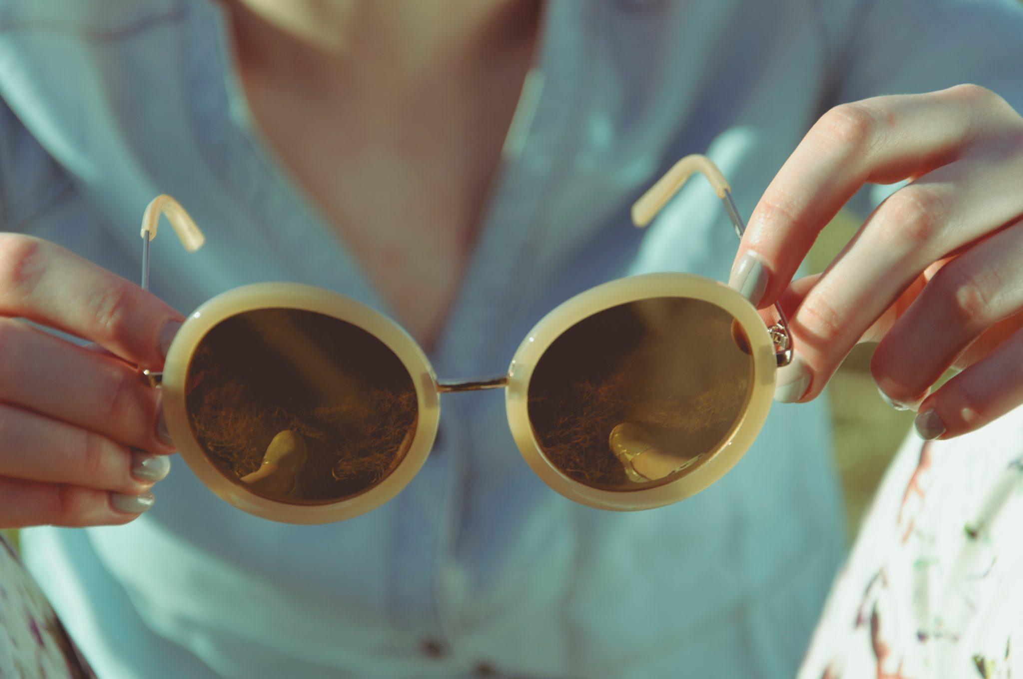 Image décorative - Femme tenant dans ses mains une paire de lunette de soleil