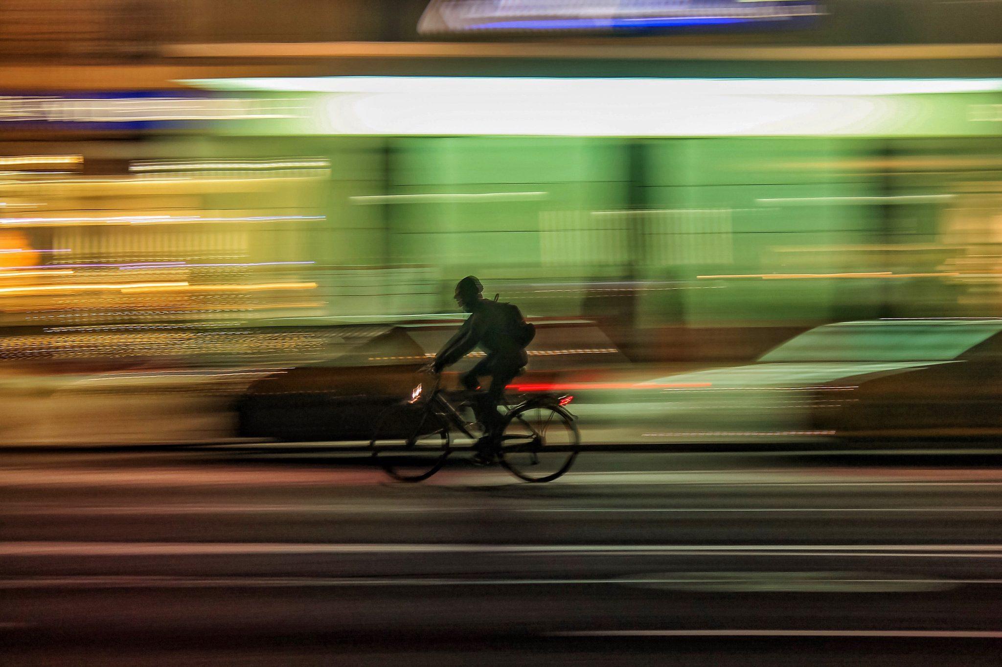 Image décorative - Personne faisant du vélo en ville de nuit