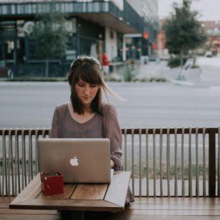 Femme travaillant en extérieur sur ordinateur dans un café