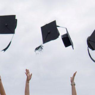 mains des étudiants avec les chapeaux