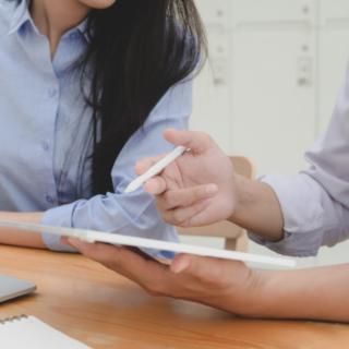 deux personnes en chemise bleue discutent avec une tablette