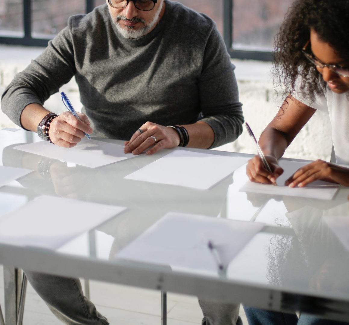 un homme et une femme en train d'écrire à une table blanche