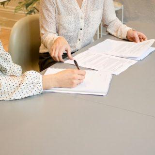 deux personnes travaillent sur des documents